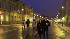 Young in love couple walks on the evening urban street. Young couple walks on the night urban illuminated street and approaches to camera. The people have a good stock footage