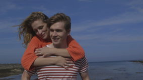 Young love. A happy young couple laugh and smile together as they walk along the beach with each other. The woman is getting a piggyback from her boyfriend and stock footage
