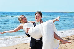 Young Love - Newly Wed. The groom holds his bride on his arms by the sea on the beach and both of them shine of happiness Stock Photos
