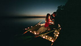 Young love romance on boat with candles at night stock footage