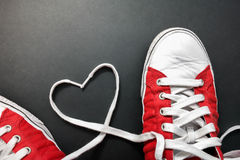 Young love. The shoelaces of some red sneakers forming a heart Stock Image