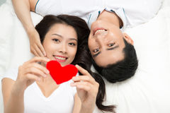 Young lovely asian couple holding red heart together lying in a bed Royalty Free Stock Photography