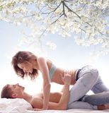 A young and lovely brunette couple laying in jeans Stock Photos
