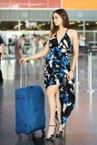 Young lovely brunette. Posing at the airport standing next to a suitcase dressed in a long dress stock images