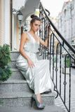 Young lovely brunette. Posing on the street near the handrail sitting on the stairs dressed in a long dress royalty free stock photos