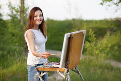 Young lovely caucasian woman painting outdoors Stock Photo