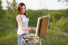 Young lovely caucasian woman painting outdoors Stock Image