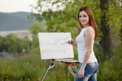 Young lovely caucasian woman painting outdoors Royalty Free Stock Image