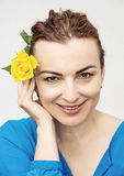 Young lovely caucasian woman with yellow rose in hair Stock Photo