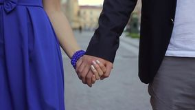 Young lovely couple holding hands and walking in a city stock video