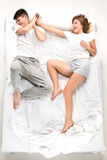 The young lovely couple lying in a bed with alarm clock Stock Photography