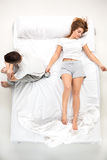 The young lovely couple lying in a bed with alarm clock Stock Images