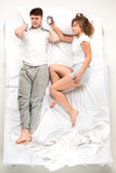 The young lovely couple lying in a bed with alarm clock Royalty Free Stock Image