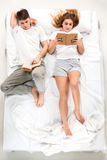 The young lovely couple lying in a bed with books Royalty Free Stock Images