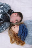 Young lovely couple lying in a bed, happy smile looking to each other. Royalty Free Stock Image