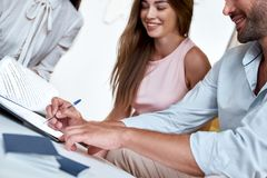 Young lovely couple signing contract for a vacation. Close-up, travel agency. Young lovely couple sitting with manager at the travel agency office and signing stock image