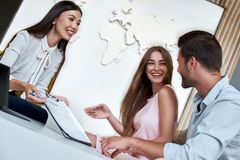 Couple sitting with manager at the travel agency office and reviewing contract. Young lovely couple sitting with manager at the travel agency office and royalty free stock image