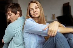 Young lovely couple sitting on the table back to back stock image