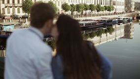 Young lovely couple staying on a bridge. And looks to water stock video footage