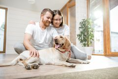 Couple with dog in the house. Young lovely couple in white t-shirts playing with their dog sitting on the floor in the house stock image