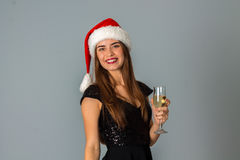 Young lovely girl in santa hat. With glass of champagne smiling on camera in studio on grey background Stock Images
