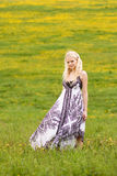 Young lovely girl standing on. Green meadow in spring royalty free stock photo