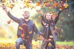 Young lovely happy couple -  lovers flying with leaves  in autumn park Stock Images