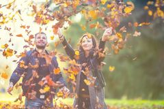 Young lovely happy couple -  lovers flying with leaves  in autumn park Royalty Free Stock Images
