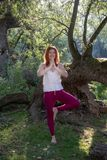 Young lovely red-haired ginger woman doing yoga exercises with hands up on one leg in nature in sportswear in the sun. Young lovely red-haired ginger woman stock image