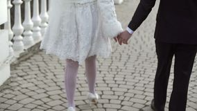 Young lovely wedding couple walking on a street stock footage