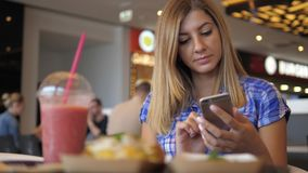 Young Lovely Woman In Blue Checkered Shirt Sits In Cafe Uses Smartphone stock footage