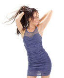 Young lovely woman in blue pleated sun-dress. Playing with hairs, studio portrait on white Royalty Free Stock Image
