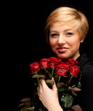 Young lovely woman with a bouquet of red roses Royalty Free Stock Photography