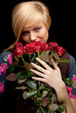 Young lovely woman with a bouquet of red roses Stock Photo