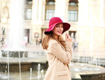 Young lovely woman in coat and purple hat on street tourist town Stock Photo