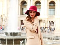 Young lovely woman in coat and purple hat on street tourist town Royalty Free Stock Photos