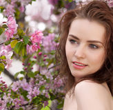Young lovely woman in spring flowers Stock Images