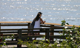Young Lovers. Young couple talking in the sun over looking the sparking waters stock images