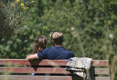 Young lovers. A young couple sitting on a bench in the summer sun relaxing and talking Stock Images