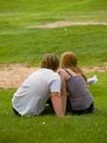 Young Lovers. A young couple sitting on the Grass in a park Stock Photography