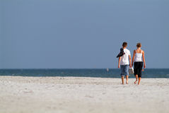 Young Lovers. Young teen lovers walking down the beach on a sunny  afternoon Stock Photos