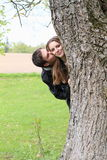 Young lovers behind a tree Stock Image