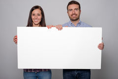 Young lovers couple holding a white cardboard. Isolated on gray background Stock Image