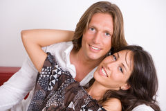 Young lovers embraced on the couch royalty free stock photos