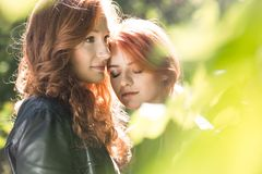 Young lovers in the forest. Young, rebellious, homosexual lovers standing in the forest. Lesbian relationship concept royalty free stock photography