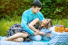Young lovers have a couple on the picnic. The guy and the girl r. Est in the park. The concept is love, family, lifestyle and healthy food Stock Image