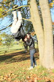 Young lovers kiss. Young men kissing a girl while hanging on branch of maple tree as spidarman Royalty Free Stock Photo