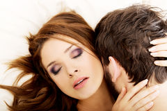 Young lovers kissing on the bed. Royalty Free Stock Images
