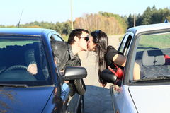 Young lovers kissing in cars. Young men kissing a girl from window of a car to a window of another car Royalty Free Stock Images