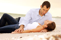Young lovers laying at beach looking at each other. Attractive young couple laying on the beach having a conversation, their clothes are wet from the ocean and Stock Photography